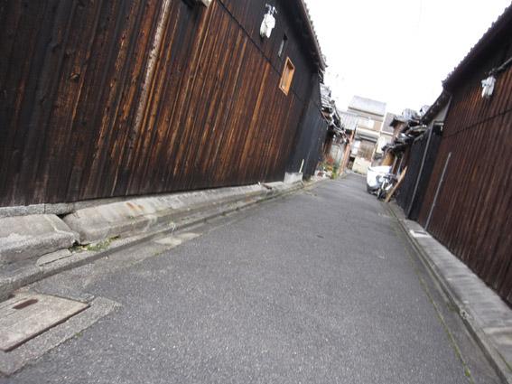 狭い路地の両側に古い木壁続く